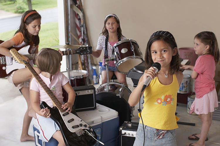 Girl Singing Into Microphone With Friends Playing Musical Instru